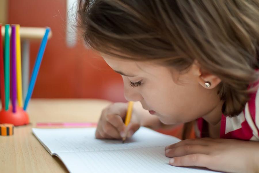 Le geste associé au tracé d'une lettre en favorise la reconnaissance en situation de lecture. Shutterstock